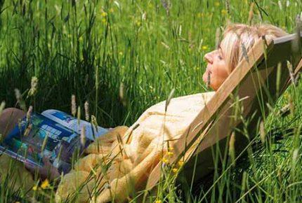 Frau-entspannt-auf-Wiese